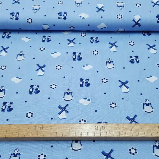 Tela OUTLET Algodón Holanda Molinos - Tela de algodón con dibujos de temática holandesa, en el que encontramos molinos, zuecos de madera, personajes de vestimenta típica holandesa, flores y topos sobre un fondo azul. La tela mide 150cm de ancho y su comp