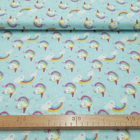Tela Algodón Unicornios Nubes Arcoiris - Preciosa tela de algodón infantil de temática unicornios y nubes con arcoiris sobre un fondo azul suave. La tela mide 150cm de ancho y su composición 100% algodón