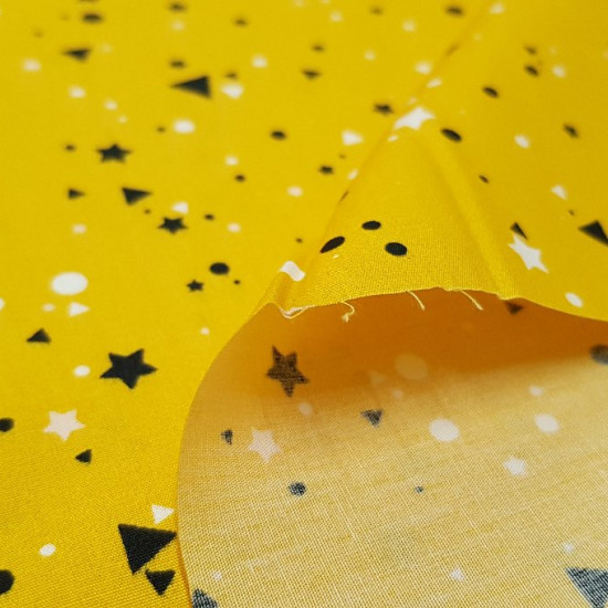 Tela Algodón Formas Geométricas - Tela de algodón con dibujos de formas geométricas (triángulos, círculos y estrellas) de colores blancos y negros sobre un fondo amarillo mostaza. La tela mide 150cm de ancho y su composición 100% algodón.