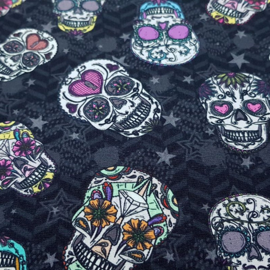 Cotton Mexican Skulls Stars Background fabric - Digital print cotton fabric with drawings of beautiful and colorful Mexican skulls on a black and gray background with zig zag shapes and stars of various sizes. The fabric is 140cm wide and its composition