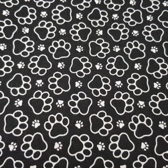 Cotton Footprints Dog fabric - Cotton fabric with prints of footprints in white on a black background. The fabric is 150cm wide and its composition is 100% cotton.