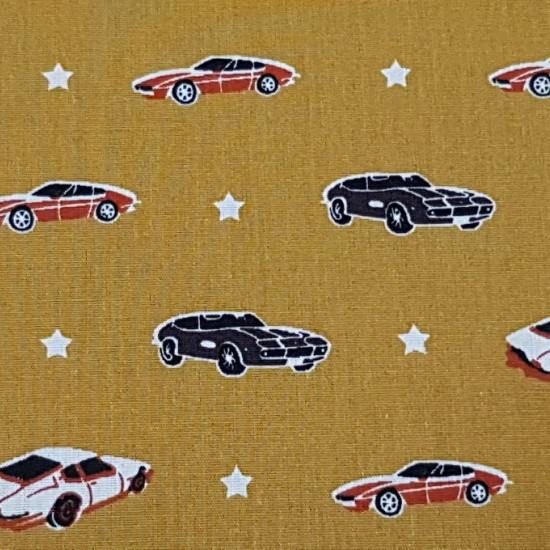 Tela Algodón Coches Estrellas - Tela de algodón con dibujos de coches Lamborghini de varios modelos y colores y también estrellas blancas intercaladas sobre un fondo ocre. La tela mide 150cm de ancho y su composición 100% algodón.