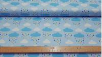 Tela Algodón Nubes Lluvia Colores - Tela de algodón ancho americano con dibujos de nubes blancas y azules con gotas de lluvia multicolor, sobre un fondo azul claro. La tela mide 110cm de ancho y su composición 100% algodón.