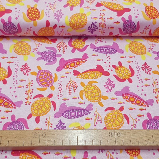 Tela Algodón Tortugas Fondo Rosa - Tela de algodón con dibujos de tortugas de coloresnadando sobre un fondo rosa con peces y corales. La tela mide 110cm de ancho y su composición 100% algodón.