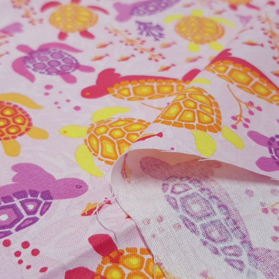 Cotton Turtles Pink Background fabric - Cotton fabric with drawings of colorful turtles swimming on a pink background with fish and corals. The fabric is 110cm wide and its composition is 100% cotton.