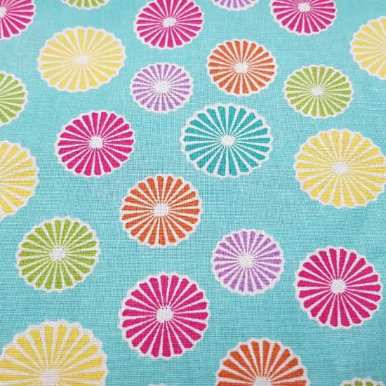 Tela Algodón Fiesta del Té Sombrillas - Tela de algodón con dibujos de remolinos o sombrillas de colores sobre un fondo de color azul claro. La tela mide 110cm de ancho y su composición 100% algodón.