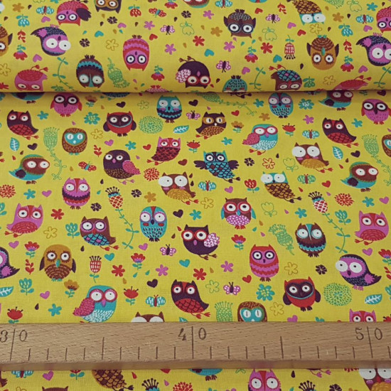 Cotton Owls Colors Mustard fabric - Cotton fabric with drawings of colored owls on a mustard background with flowers. This fabric is part of The Craft Cotton Company's Happy Owls collection The fabric is 110cm wide and its composition is 100% c