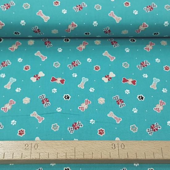 Tela Algodón Navidad Perruna Huesos - Tela de algodón navidad ancho americano con dibujos de huesos envueltos como regalo y huellas de perro. La tela mide 110cm de ancho y su composición 100% algodón.