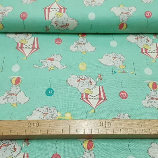 Tela Algodón Disney Dumbo - Tela de algodón de la entrañable película de Dumbo de Disney. En la tela aparecen los dibujos del elefante Dumbo y varios elementos del circo como balones, carpas de circo, globos... sobre un fondo verdeclaro. La te