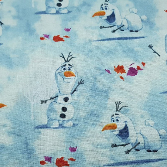 Cotton Disney Frozen 2 Olaf fabric - Disney digital cotton fabric with the character Olaf snowman on a blue background, leaves and snowy white trees. The fabric is 110cm wide and its composition 100% cotton.