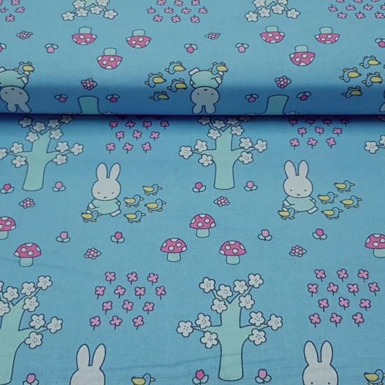 Tela Algodón Miffy Bosque - Tela de algodón licencia infantil con dibujos del personaje Miffy con unos patitos de paseo por el bosque. Aparece la conejita Miffy sobre un fondo azul con árboles, plantas y setas. La tela mide 110cm de ancho y su