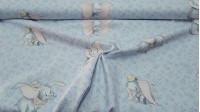Cotton Disney Dumbo Floral fabric - Disney licensed cotton fabric with drawings of the character Dumbo, the elephant with big ears, on a light blue-gray background and floral drawings. The fabric is 140cm wide and its composition is 100% cotton.