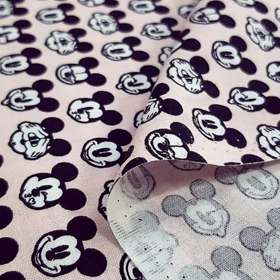 Cotton Disney Mickey Faces Pink fabric - Disney licensed cotton fabric with drawings of Mickey's faces making faces on a light pink background. The fabric is 110cm wide and its composition is 100% cotton.
