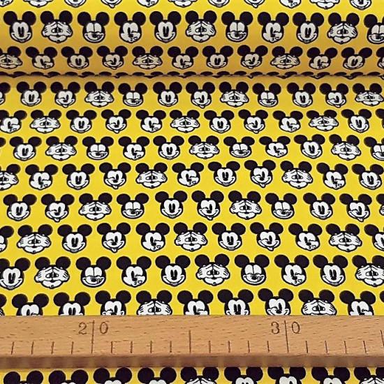 Tela Algodón Disney Mickey Caras Amarillo - Tela de algodón licencia Disney ancho americano con dibujos de caras de Mickey haciendo muecas sobre un fondo amarillo. La tela mide 110cm de ancho y su composición 100% algodón.