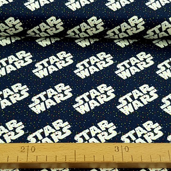 Cotton Star Wars Rainbow Logos fabric - Cotton fabric licensed Star Wars where logos appear on a navy blue background with tiny multicolored polka dots. The fabric is 110cm wide and its composition is 100% cotton.