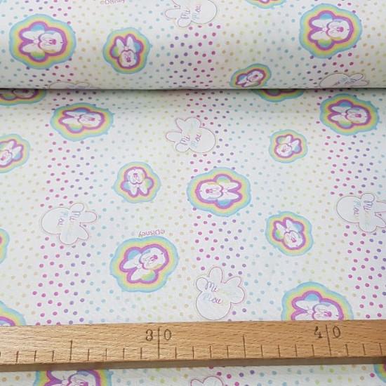 Tela Algodón Disney Minnie Multicolor Topitos - Tela de algodón licencia Disney con dibujos de la ratita Minnie coloreada sobre un fondo blanco con topitos multicolor efecto arcoiris. La tela mide 150cm de ancho y su composición 100% algodón.