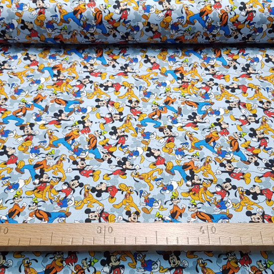 Cotton Disney Characters Collage Blue fabric - Licensed cotton poplin fabric with drawings of Disney characters such as Mickey Mouse, Goofy, Donald, Pluto... forming a collage on a light blue background. The fabric is 140cm wide and its composition is 100