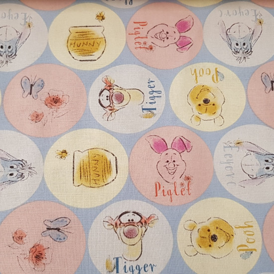 Cotton Disney Winnie Circles fabric - Disney cotton fabric with drawings of the characters of Winnie the Pooh. The characters Winnie, Tigger, Igor and Tiglet appear in circles of various colors.
