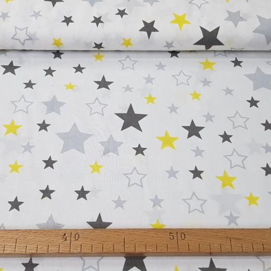 Cotton Decorative Stars fabric - Cotton fabric with decorative patterns of gray and yellow stars on a white background. The fabric is 160cm wide and its composition is 100% cotton.