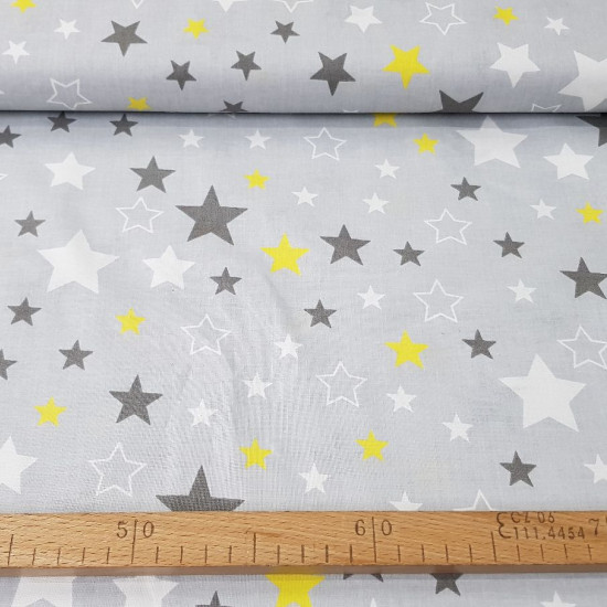 Cotton Decorative Stars Gray fabric - Cotton fabric with decorative patterns of white, dark gray and yellow stars on a gray background. The fabric is 160cm wide and its composition is 100% cotton.