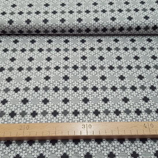 Tela Algodón Cuatro Pétalos - Tela de algodón con dibujos de flores de cuatro pétalos entrelazadas en tonos de colores blanco, negro y gris. La tela mide 150cm de ancho y su composición 100% algodón.