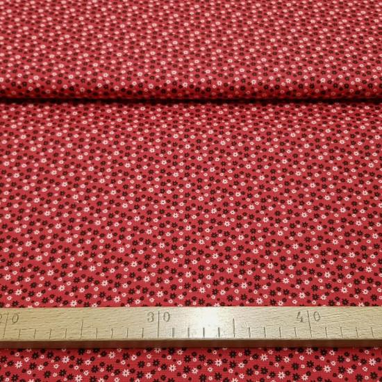 Tela Algodón Flores Margaritas Rojo - Tela de algodón con dibujos de flores con forma de margarita de colores blanco y negro sobre un fondo rojo. La tela mide 140cm de ancho y su composición 100% algodón.