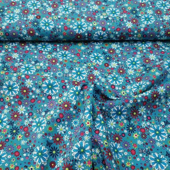 Tela Algodón Flores Colores Mariposas - Tela de algodón con dibujos de flores de varios tamaños y colores sobre un fondo azul petroleo con mariposas. La tela mide 140cm de ancho y su composición 100% algodón.