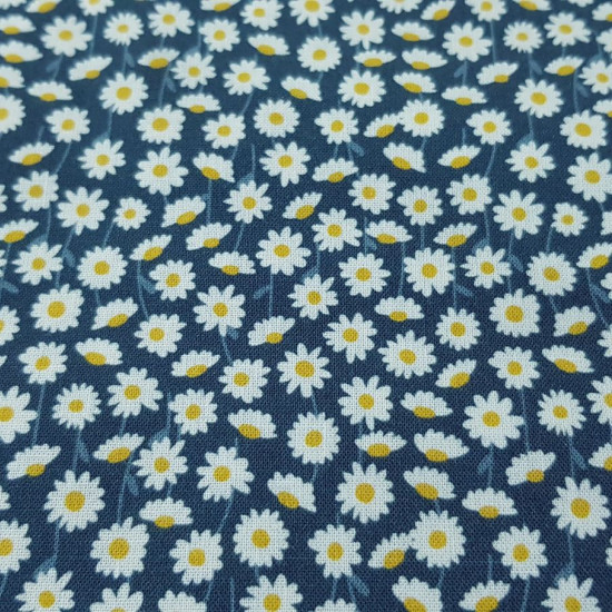 Cotton Fabby Daisies fabric - Organic cotton fabric with drawings of daisies on a blue background. The fabric is 150cm wide and its composition is 100% cotton.