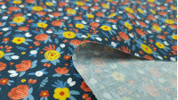 Cotton Flowers Flua Blue fabric - Organic cotton fabric with drawings of various colored flowers on a blue background. The fabric is 150cm wide and its composition is 100% cotton.
