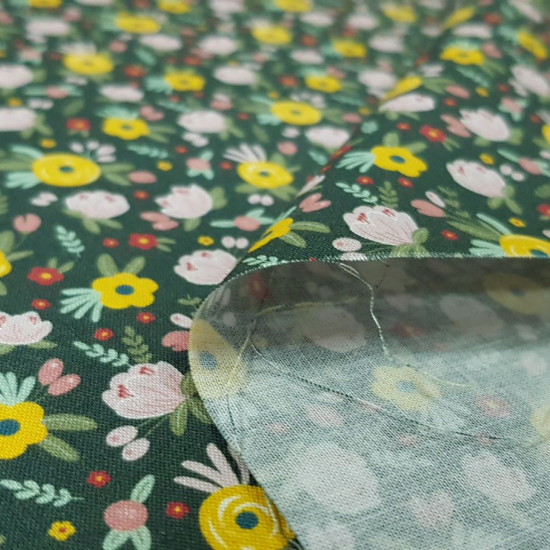 Cotton Flowers Flua Green fabric - Organic cotton fabric with drawings of various types of flowers in various colors on a dark green background. The fabric is 150cm wide and its composition is 100% cotton.