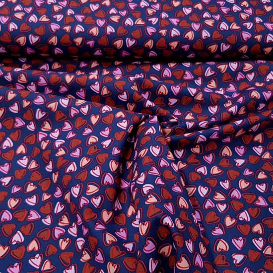 Tela Algodón Corazones Allover Marino - Tela de algodón con dibujos de corazones pequeños en varios colores de tonos rojos y rosassobre un fondo azul marino. La tela mide 150cm de ancho y su composición 100% algodón.