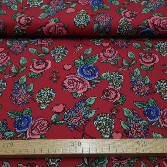 Tela Algodón Rosas y Calaveras - Tela de algodón muy original con dibujos de rosas y calaveras (calacas)en multicolor sobre un fondo rojo oscuro.