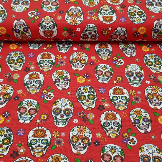 Cotton Mexican Skull Calacas Grey - Printed cotton fabric with drawings of calacas or skulls typical of the Day of the Dead in a variety of colors and a flowered red background.