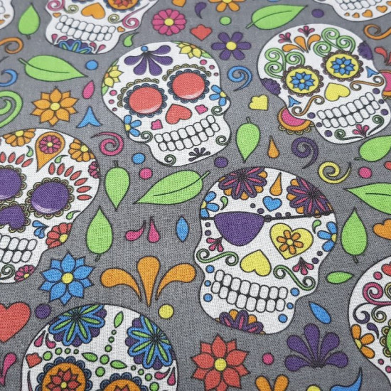 Cotton Mexican Skull Calacas Grey - Printed cotton fabric with drawings of calacas or skulls typical of the Day of the Dead in a variety of colors and a flowered gray background.
