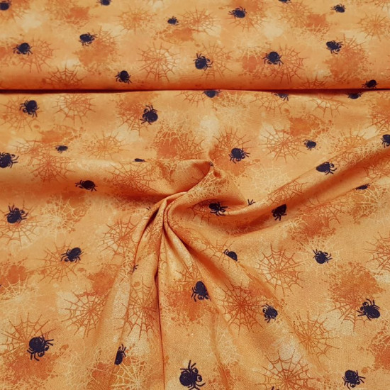 Cotton Halloween Cobwebs Orange Background fabric - Cotton fabric with drawings of spider webs and spiders of various sizes on an orange background. The fabric is 150cm wide and its composition 100% cotton.