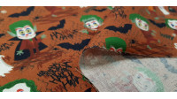 Cotton Halloween Green Hairs fabric - Organic cotton fabric with Halloween-themed drawings where different monsters appear with green hair and their faces painted in the Joker style, on an orange-brown background with bats. The fabric is 150cm wide and i