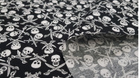 Cotton Skulls Pirate Saber fabric - Cotton fabric with drawings of pirate skulls with crossed sabers on a black background. The fabric is 140cm wide and its composition is 100% cotton.