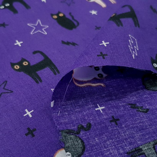 Tela Polycotton Halloween Gatos Violeta - Tela fina de poliester y algodón con dibujos dehalloween con gatos negros y blancos sobre un fondo violeta con rayos y estrellas. La tela mide 110cm de ancho y su composición 80% poliester – 20% algodón.