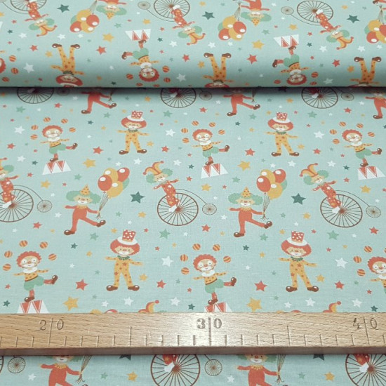 Cotton Circus Clowns Green fabric - Circus themed cotton fabric with drawings of clowns on unicycles, climbed on trampolines, juggling ... on a sea green background. The fabric is 150cm wide and its composition 100% cotton.