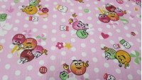 Cotton Balls Chocolate M Pink fabric - Very funny cotton poplin fabric with drawings of the famous colorful M&Ms® chocolate balls on a pink background with white polka dots. The fabric is 150cm wide and its composition 100% cotton.