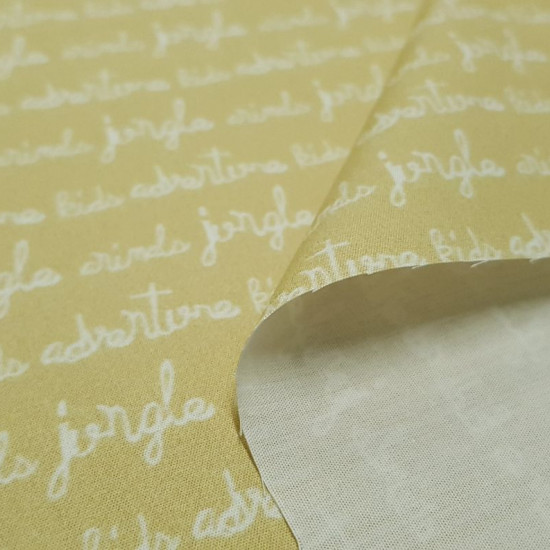 Cotton Childrens Letters Yellow fabric - Organic cotton poplin fabric with drawings of children's calligraphy texts on a yellow background. The fabric is 150cm wide and its composition is 100% cotton.