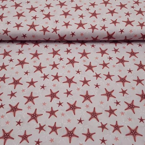 Tela Algodón Estrella de Mar - Tela de algodón orgánico de temática marinera o de verano, con dibujos de estrellas de mar de color rojo coralsobre un fondo rosa clarito. La tela mide 150cm de ancho y su composición 100% algodón.
