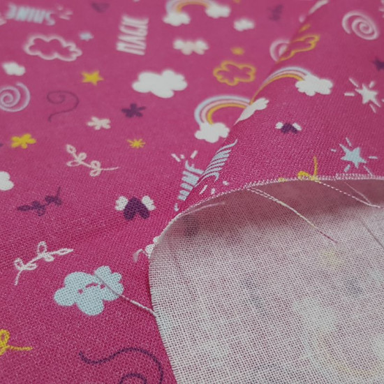 """Tela Algodón Nubes Arcoiris Dream - Tela de algodón infantil con dibujos de nubes con arcoiris, diamantes, garabatos y frases """"dream"""", """"shine"""" y """"magic"""" sobre un fondo rosa fucsia. La tela mide 150cm de ancho y su composición 100% algodón."""