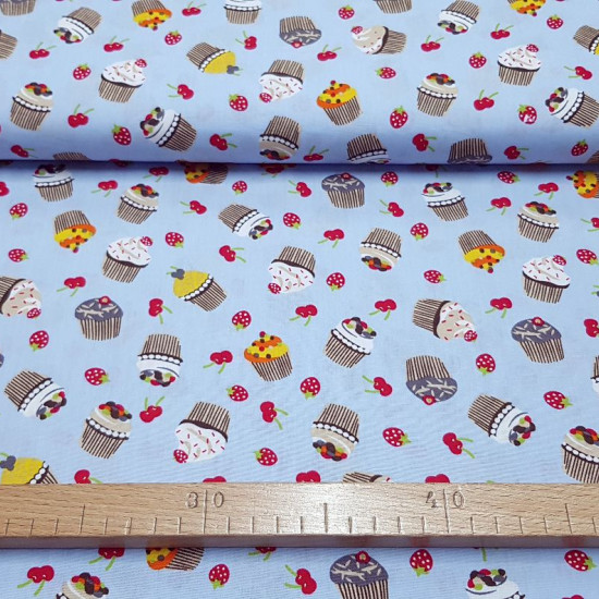 Cotton Cupcakes Fruits Blue fabric - Cotton fabric with drawings of cupcakes and red fruits, cherries and strawberries, on a light blue background The fabric is 150cm wide and its composition is 100% cotton.