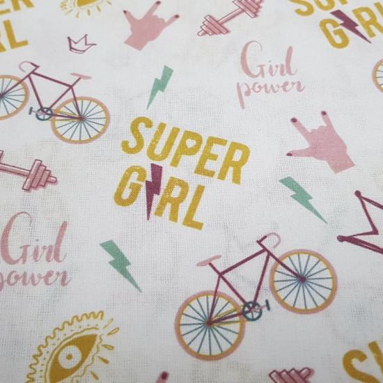 """Tela Algodón Super Girl - Tela de algodón orgánico con dibujos en varios colores de bicicletas, rayos, pesas de gimnasio, coronas y frases """"Girl Power"""" y """"Super Girl"""" sobre un fondo de color blanco. La tela mide 150cm de ancho y su composició"""