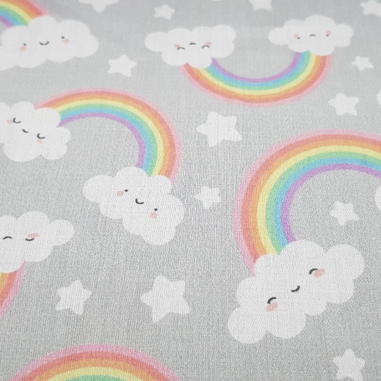 Cotton Rainbow Smiley Clouds fabric - Satin cotton fabric with drawings of rainbows, smiling clouds and stars on a light gray background. The fabric is 140cm wide and its composition is 100% cotton.