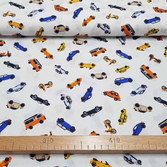 Tela Algodón Coches Colores - Tela de algodón con dibujos de coches de varios colores sobre un fondo blanco. La tela mide 150cm de ancho y su composición 100% algodón.