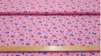 Tela Algodón Lenguas Rayos - Tela de algodón tipo popelín con dibujos de bocas con la lengua fuera y decorado con estrellas, rayos y otros símbolos sobre un fondo rosa. La tela mide 145cm de ancho y su composición 100% algodón.
