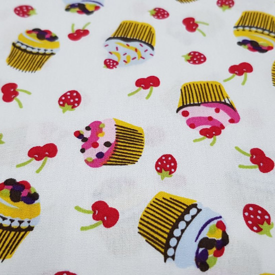 Cotton Cupcakes Fruits fabric - Cotton fabric with drawings of cupcakes and red fruits, cherries and strawberries, on a white background The fabric is 150cm wide and its composition is 100% cotton.