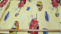 Tela Algodón Coches Carreras - Tela de algodón decorativa con dibujos de coches grandes de carreras sobre un fondo amarillo claro. La tela mide 160cm de ancho y su composición 100% algodón.